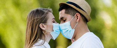 Couple with mask kissing at park