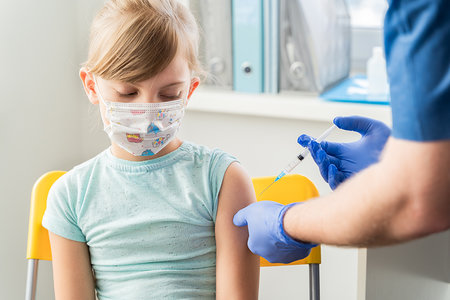 Little girl in the doctor's office is vaccinated. Syringe with vaccine against covid-19 coronavirus,flu,dangerous infectious diseases.Injection after clinical trials for human, child.Medicine concept.