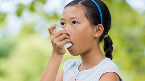 Girl using an asthma inhaler in the park