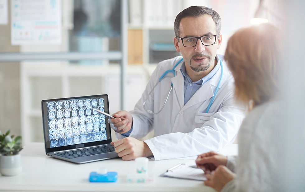 Male doctor explaining the illness to his patient and pointing at laptop with x-ray images while they sitting at the table at office
